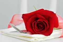 Rose y cubiertos rojos Foto de archivo libre de regalías