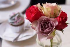 Rose y la flor y la taza se apelmazan detrás en café Imágenes de archivo libres de regalías