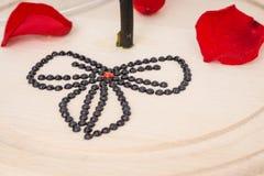 Rose y pétalos con el corazón rojo de diamantes artificiales imagen de archivo libre de regalías