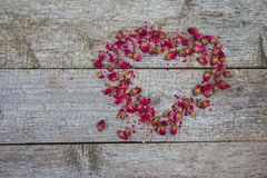 Rosebuds on rustic wooden table in shape of heart Stock Image