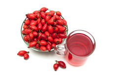 Rosehip berries and drink in a circle on a white background Stock Photo