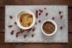 Rosehip berries and medical herbs in a white bowl on a concrete slab. Dark background stock photography