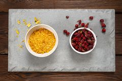 Rosehip berries and medical herbs in a white bowl on a concrete slab. Wooden background stock photography