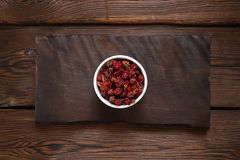 Rosehip berries in a white bowl on a wooden slab. Wooden background royalty free stock photos