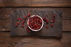 Rosehip berries in a white bowl on a wooden slab. Wooden background royalty free stock images