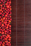 Rosehip on a dark  bamboo mat Stock Image