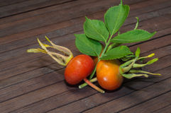 Rosehip. Delicious rosehip and leaf laying on a brown cutting board Royalty Free Stock Photo