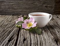 Rosehip flowers and cup of healthy tea, herbal medicine. A cup of  tea with rosehip on the wooden background. Rustic style stock image