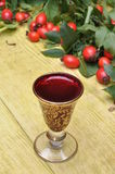 Rosehip fruit and alcoholic liquor in a glass Royalty Free Stock Photography