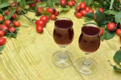 Rosehip fruit and alcoholic liquor Royalty Free Stock Photos
