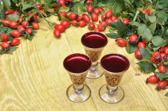 Rosehip fruit and alcoholic liquor Stock Images