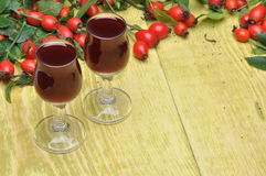 Rosehip fruit and liquor in a glasses Stock Images