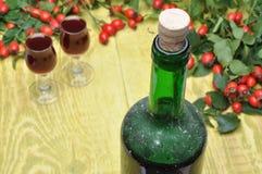 Rosehip owoc i alkoholiczka trunek w butelce i szkłach obraz royalty free
