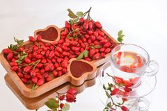 Rosehip products; jam and herbal tea. Rosehip served on a bamboo plate, jam, marmalade and tea stock image