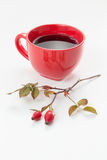 Rosehip (Rosa canina). Fresh rosehips with a cup of rosehip tea Royalty Free Stock Photo