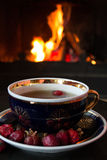Rosehip tea in front of roaring fire in a fire place Royalty Free Stock Image