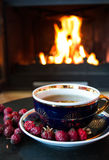 Rosehip tea in front of roaring fire in a fire place Royalty Free Stock Photo