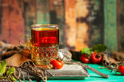 Rosehip tea. Glass of rosehip tea in a silver glass-holder and fresh berries royalty free stock photo