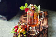 Rosehip tea in glass on black stone background Stock Image