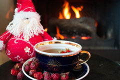 Rosehip tea with snowman in front of roaring fire in a fire place Royalty Free Stock Photo