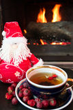 Rosehip tea with snowman in front of roaring fire in a fire place Stock Photo