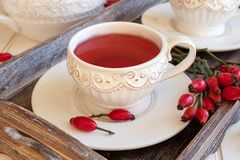Rosehip tea in white vintage cups with fresh berries royalty free stock photography