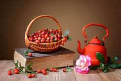 Rosehip in wicker baskets, book, rose and a teapot Stock Photography
