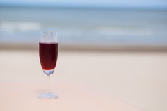 Roselle juice with beach view. Glass of roselle juice with beach view royalty free stock images