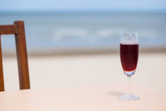 Roselle juice with beach view. Glass of roselle juice with beach view stock photo
