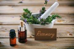 Rosemary-ätherisches Öl und frischer blühender Zweig in einem Mörser, Holztisch, Tag mit Textrosmarin stockfoto