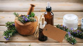 Rosemary Aromatherapy Aceite esencial y cosméticos, etiqueta en blanco, bandera Fondo de madera de la tabla fotografía de archivo libre de regalías