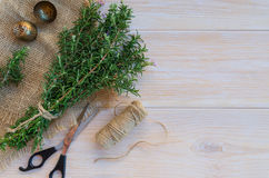 Rosemary background. Bunch of fresh rosemary with purple flowers, thread reel, scissors, vintage tea infuser in sacking napkin on wooden background.  Rustic Stock Photos