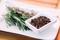 Rosemary with black pepper corns on a white plate Stock Images