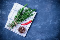 Rosemary braches tied. Rosemary branches tied with string on concrete dark blue table background. With pepper blend and chili pepper on white cloth napkin. Top Royalty Free Stock Photography