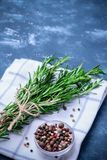 Rosemary braches tied. Rosemary branches tied with string on concrete dark blue table background. With pepper blend on white cloth napkin. Cooking concept Stock Image