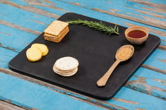 Rosemary, cheese and biscuits with spices on slate board Royalty Free Stock Photos