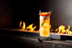 Rosemary cocktail on fireplace. A cocktail on fireplace with fire on background Stock Photo