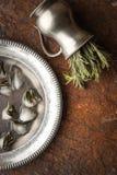 Rosemary in de vaas met ijsblokjes in het metaal plateert verticaal Stock Foto's