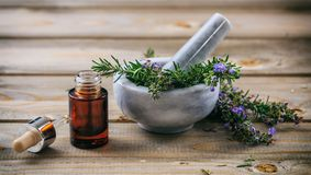 Rosemary essential oil and fresh blooming twig in a mortar, wooden table stock photography