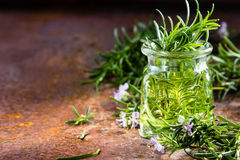 Rosemary essential oil jar glass bottle and branches of plant. Rosemary oil. Rosemary essential oil jar glass bottle and branches of plant rosemary with flowers stock images