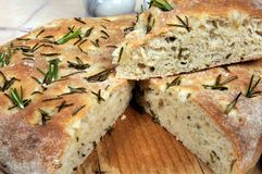 Rosemary flavoured Italian Focaccia bread. Homemade Italian rosemary Focaccia bread with wedge cut out tok reveal the inside Royalty Free Stock Image