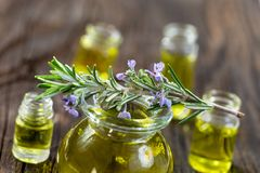Rosemary in flower on top of an aromatherapy essential oil blue glass bottle , over white background royalty free stock photography