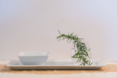 Rosemary in a glass of water on table. Fresh rosemary sprig in a glass of water Royalty Free Stock Photos