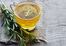 Rosemary herbal tea in a glass cup with fresh green rosemary herb on rustic wooden background. Selective focus royalty free stock photography