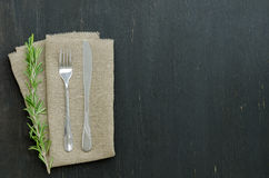 Rosemary with knife and fork. Lying on the linen napkin. Copy-space composition Stock Images