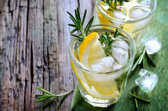 Rosemary and lemon soda. Lemon and rosemary soda with ice cubes in glasses or maybe refreshing summer alcoholic cocktail Stock Images