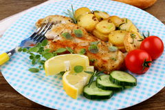 Rosemary potatoes with fried fish fillet and vegetables Stock Photos
