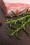 Rosemary and raw pork in vertical format Royalty Free Stock Images