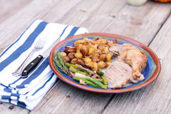 Rosemary roasted duck. Stuffed with bread stuffing and ringed with asparagus in a pottery dish during the holiday season royalty free stock photography