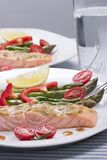 Rosemary Roasted Salmon. Served with asparagus, cherry tomatos, red bell pepper topped by mustard rosematy sauce and glass of ice water for healthy style dinner stock image